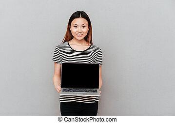vrouw, draagbare computer, vrijstaand, vrolijk, vasthouden, blank lichten door