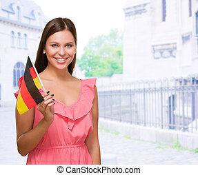 vrouw, duitser, jonge, vlag, vasthouden, vrolijke