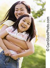 vrouw, en, jong meisje, buitenshuis, omhelzen, en, het glimlachen