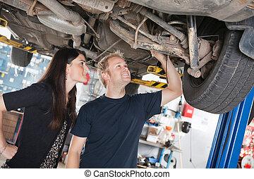 vrouw, en, werktuigkundige, kijken naar, auto, verstelt