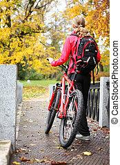 vrouw, fietser, met, fiets, en, schooltas, in, herfst, park