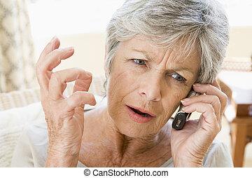 vrouw, frowning, telefoon, binnen, cellulair, gebruik