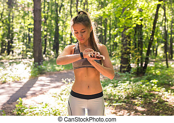 vrouw, gebruik, activiteit, tracker, of, gehoorde snelheid, monitor., buiten, fitness, concept.