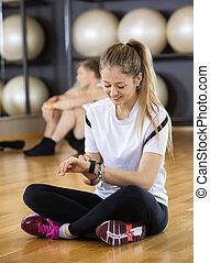 vrouw, gebruik, activiteit, tracker, terwijl, zittende , in, gym