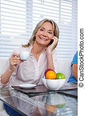 vrouw, gebruik, mobiele telefoon, op, ontbijttafel