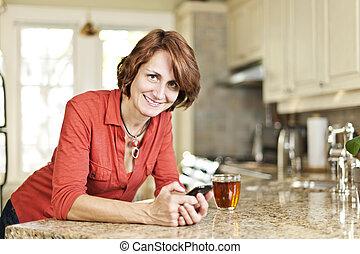 vrouw, gebruik, mobiele telefoon, thuis