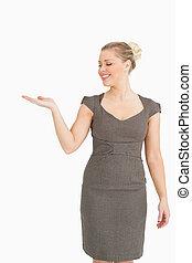 vrouw glimlachen, het voorstellen, iets, met, haar, hand