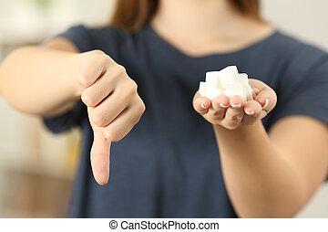 vrouw, hand houdend, suikerklontjes, met, beduimelt neer