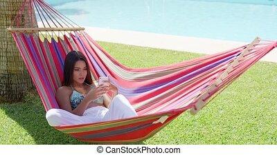 vrouw, het bepalen, in, hangmat, terwijl, gebruik, telefoon
