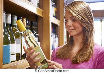 vrouw, het kiezen van fles, van, witte wijn, in, supermarkt