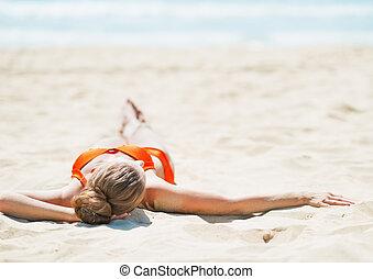 vrouw, het leggen, jonge, strand., achterk bezichtiging