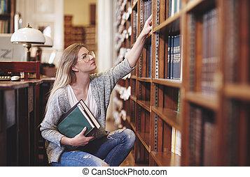vrouw, het onderzoeken, boekjes , in, bibliotheek