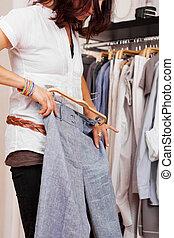 vrouw, het proberen, trouser, in, de opslag van de kleding