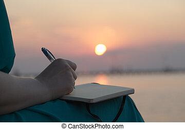 vrouw het schrijven, in, haar, dagboek, op, ondergaande zon