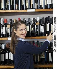 vrouw, het selecteren, wijn fles, van, plank, in, supermarkt