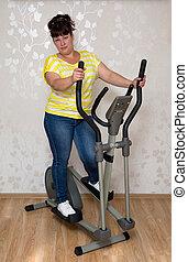 vrouw, het uitoefenen, op, trainer, ellipsoid