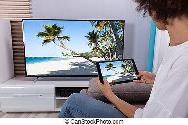 vrouw, het verbinden, tv, door, wi-fi, op, digitaal tablet