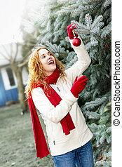 vrouw, het verfraaien van de boom van kerstmis, buiten