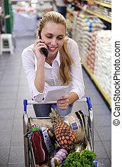 vrouw, in, de, supermarkt, het spreken op de telefoon, met, het winkelen lijst