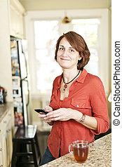 vrouw, in, keuken, met, mobiele telefoon