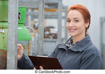vrouw, in, metaal, magazijn, controleren, producten