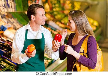 vrouw, in, supermarkt, en, winkelbediende