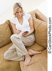 vrouw, in, woonkamer, gebruik, persoonlijke digitale assistent, het glimlachen