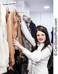 vrouw, kies, jas, op, de opslag van de kleding