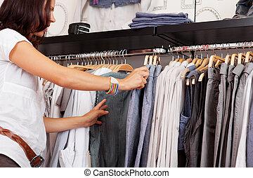vrouw, kies, trouser, van, rek, in, de opslag van de kleding