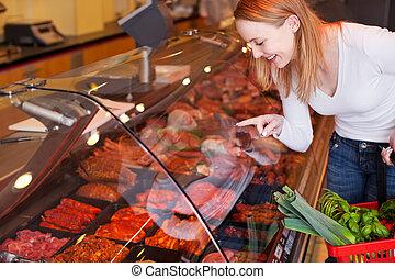 vrouw, kies, vlees, van, glas, kabinet, in, grocery slaan op