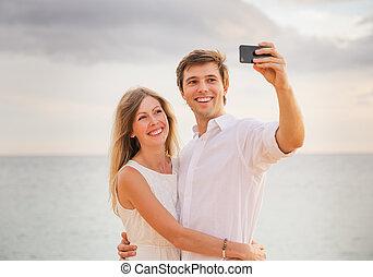vrouw, liefde, romantische, foto, paar, telefoon, boeiend, zich, vrolijke , strand, ondergaande zon , smart, man
