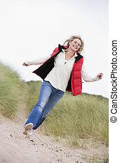 vrouw lopend, op, strand, het glimlachen