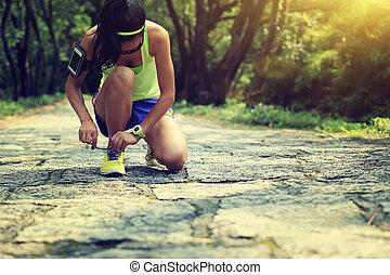 vrouw, loper, jonge, spoor, bos, het verbinden shoelaces