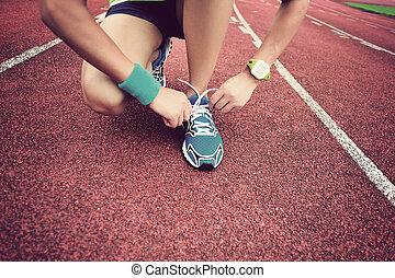 vrouw, loper, jonge, voetspooren, het verbinden shoelaces