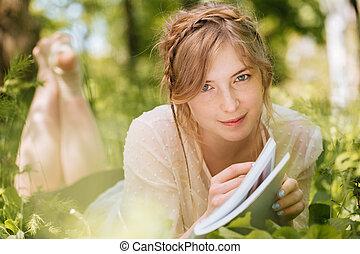 vrouw, magazine, buitenshuis, het glimlachen, gras, het liggen