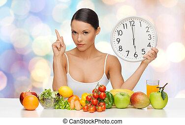 vrouw, met, gezond voedsel, en, klok, waarschuwend