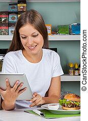 vrouw, met, hapjes, bij lijst, gebruik, tablet, in, winkel