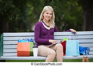 vrouw, met, het winkelen zakken, en, tablet pc, buitenshuis