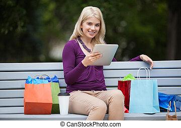 vrouw, met, het winkelen zakken, gebruik, tablet pc, buitenshuis