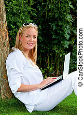 vrouw met laptop computer, in de tuin