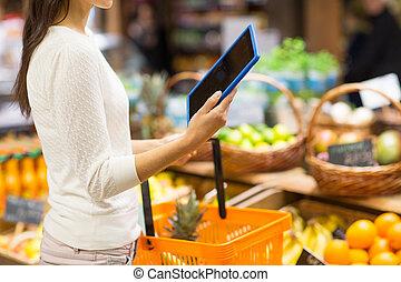vrouw, met, mand, en, tablet pc, in, markt