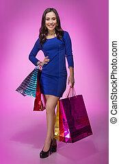 vrouw, met, shoppen , bags., volledige lengte, van, mooi, jonge vrouw , vasthouden, het winkelen zakken, en, het glimlachen, aan fototoestel, terwijl, staand, vrijstaand, op, achtergrond kleurde
