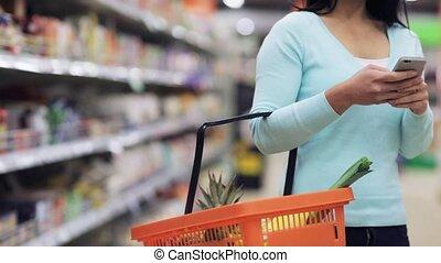vrouw, met, smartphone, en, voedingsmiddelen, mand, op,...