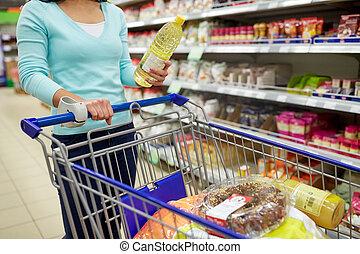 vrouw, met, voedingsmiddelen, in, boodschappenwagentje, op, supermarkt