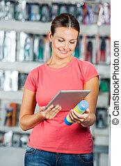 vrouw, onderzoeken nauwkeurig, product, door, digitaal tablet, in, hardware winkel