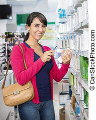 vrouw, onderzoeken nauwkeurig, streepjescode, door, smart, telefoon, in, apotheek