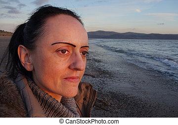 vrouw, op, strand, op, ondergaande zon