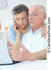 vrouw, paar, telefoon, bejaarden, draagbare computer, gebruik