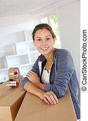 vrouw, pakking, verhuizen, jonge, dozen, het glimlachen, uit