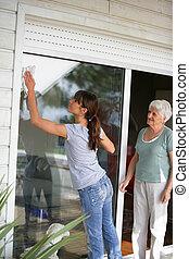 vrouw, poetsen, een, glas, patio deur, voor, een, bejaarden, dame